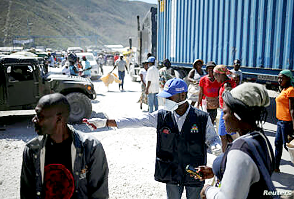 A worker with Haiti's Ministry of Public Health and Population asks a Haitian woman coming from Dominican Republic to be checked as part of measures to monitor the coronavirus in Malpasse